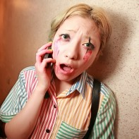 A Japanese girl busy on her cell phone takes a moment for a picture.