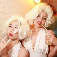 The two Marilyn Monroe cosplayers drinking together on the stairs.